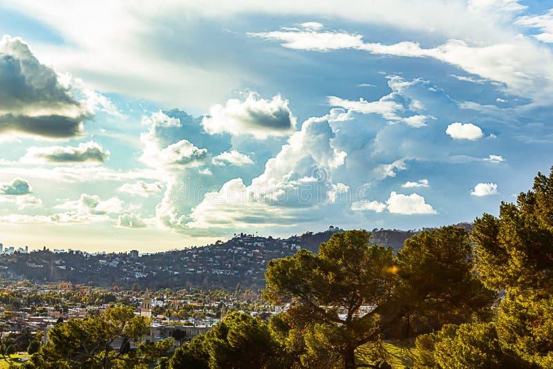 Alberi sempreverdi con la vista panaramic delle costruzioni e delle case del pendio di collina fotografie stock libere da diritti