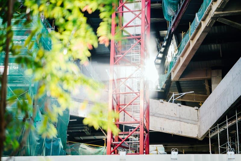 Albero coperto di foglie verde accanto alle capriate ed alla costruzione rosse del metallo fotografia stock libera da diritti