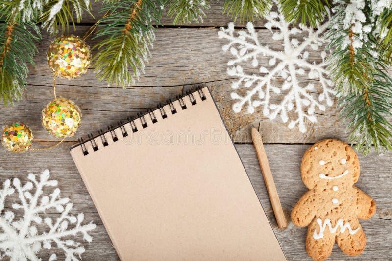 Albero di abete di Natale, decorazione e blocco note in bianco sul bordo di legno indietro immagini stock