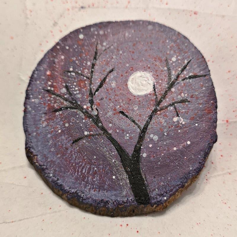 Albero di inverno sotto luminoso della luna dipinto su una fetta di legno fotografia stock