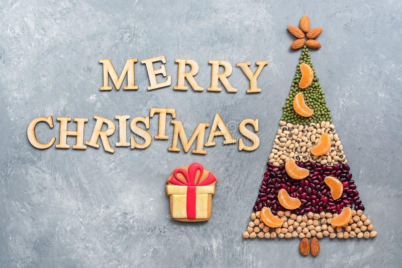 Albero di Natale astratto fatto dai vari legumi e dalle mandorle decorati con le fette di mandarino su un fondo grigio Il concett immagine stock