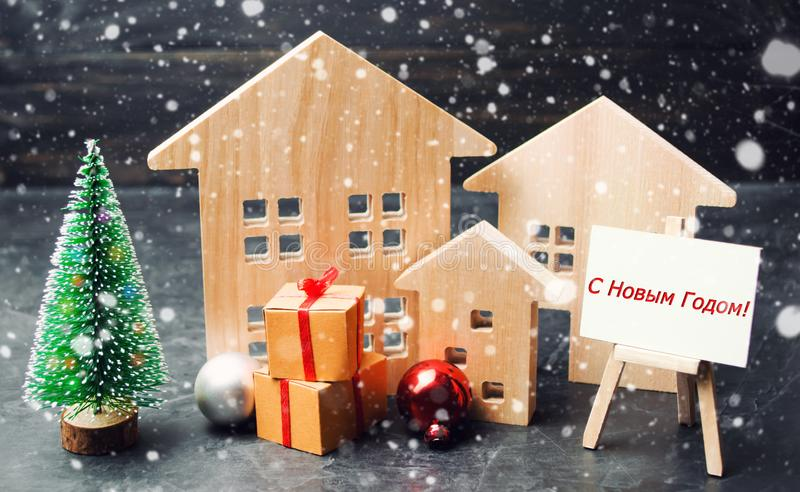 """Albero di Natale, case di legno e regali con """"l'iscrizione del buon anno e di Buon Natale 2019 """"nella lingua russa Nuovo anno C fotografia stock"""