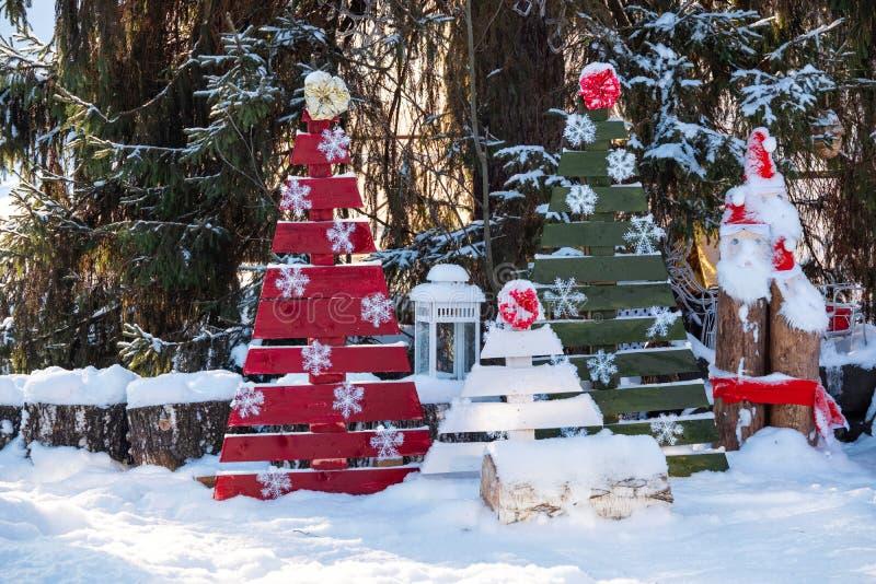 Albero di Natale con i giocattoli e la slitta nel parco della città Albero decorato fuori con le luci coperte di neve Un chiaro i immagini stock