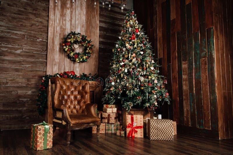 Albero di Natale decorato accanto ad una vecchia sedia marrone di cuoio lo stile d'annata scuro ha tonificato la foto fotografia stock