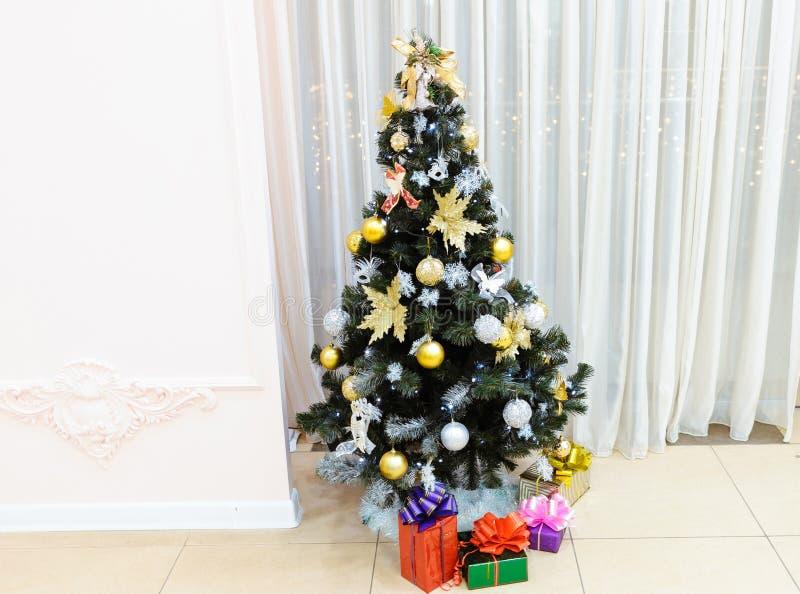 Albero di Natale decorato con i giocattoli con i regali in scatole sotto su un fondo leggero immagini stock libere da diritti
