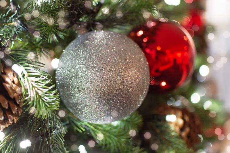 Albero di Natale decorato Palle rosse e argentate e garland con luci Foto di Capodanno con bokeh Luce festiva invernale immagini stock