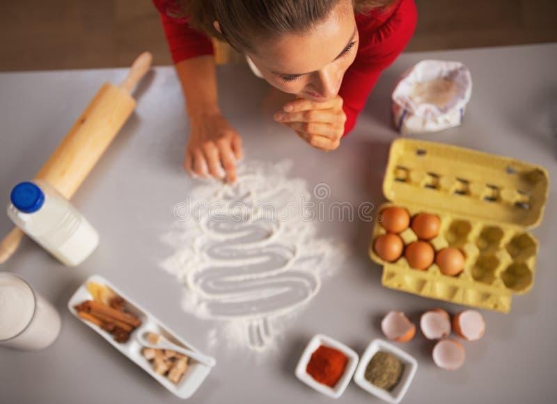 Albero di Natale del disegno della casalinga sul tavolo da cucina con farina immagine stock