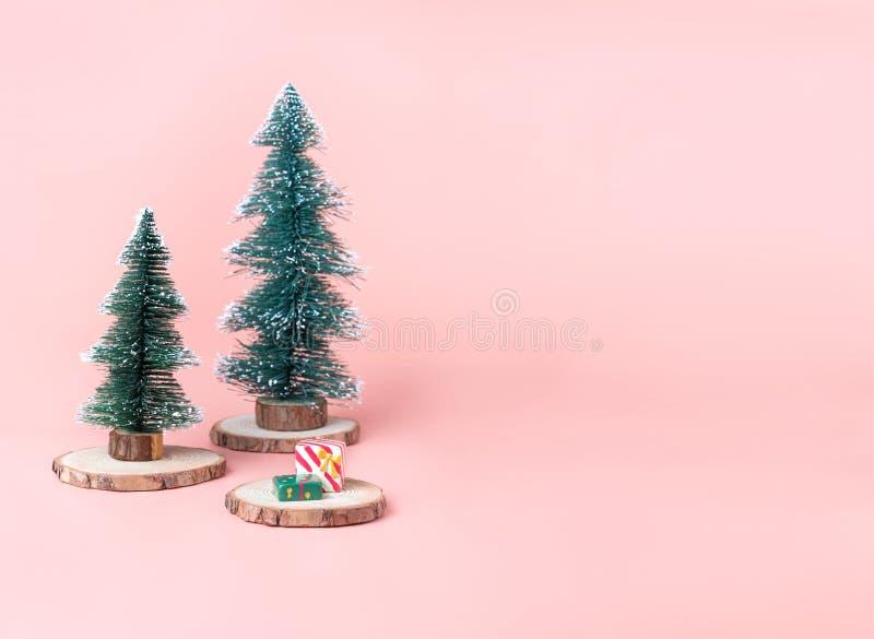 Albero di Natale dell'albero sulla fetta di legno del ceppo con la scatola attuale su pastello fotografia stock