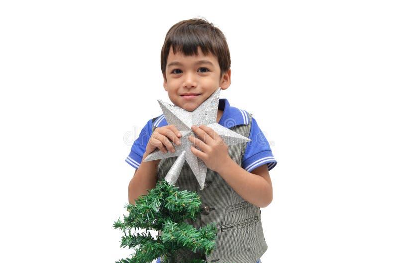 Albero di Natale della stella della tenuta del ragazzino