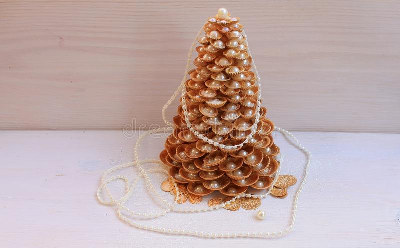 Albero di Natale dorato fatto a mano dalle conchiglie su un fondo bianco immagine stock