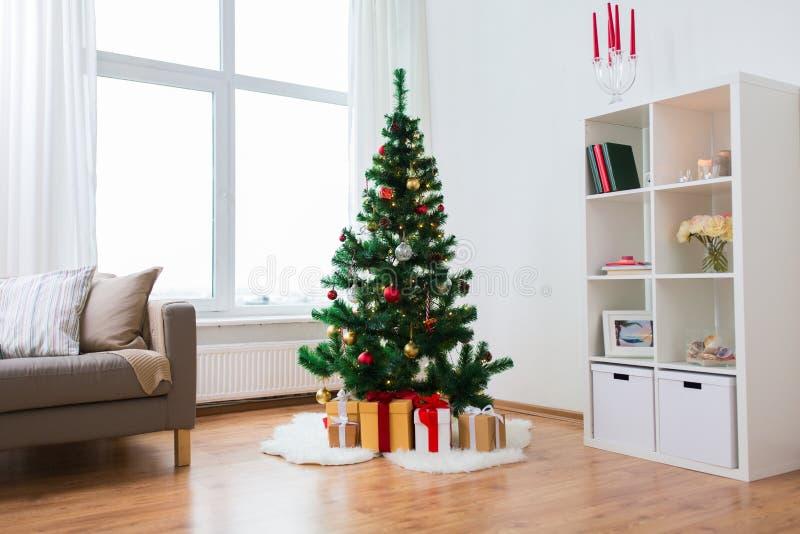 Albero di Natale e presente artificiali a casa fotografie stock libere da diritti
