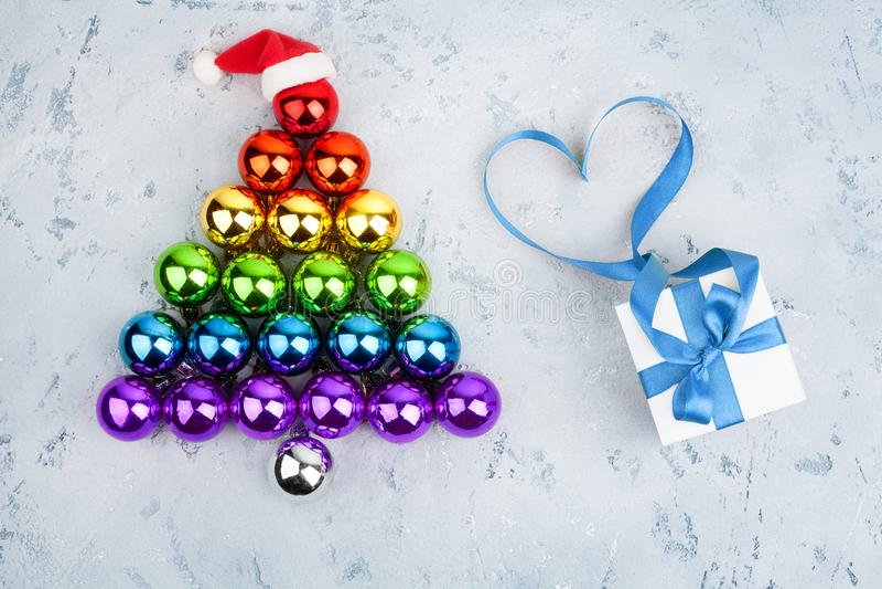 Albero di Natale fatto dei colori della bandiera dell'arcobaleno della comunità delle palle LGBT delle decorazioni, cappello di S fotografia stock