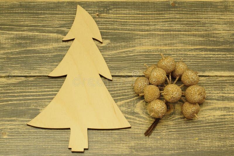 Albero di Natale fatto di legno e delle mele decorative su un fondo di legno scuro immagine stock