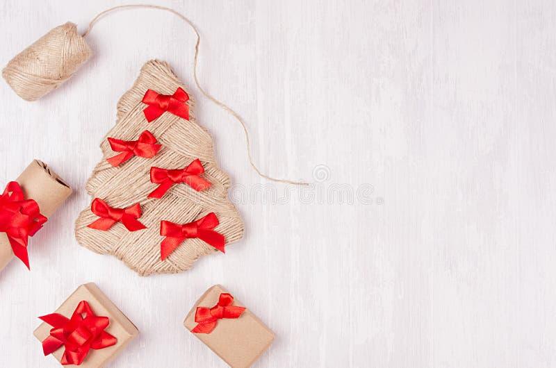Albero di Natale fatto a mano di iuta naturale decorato degli archi e dei contenitori di regalo rossi sul bordo di legno bianco m immagine stock