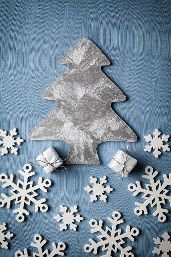 Albero di Natale, fiocchi di neve e regali su fondo blu fotografie stock
