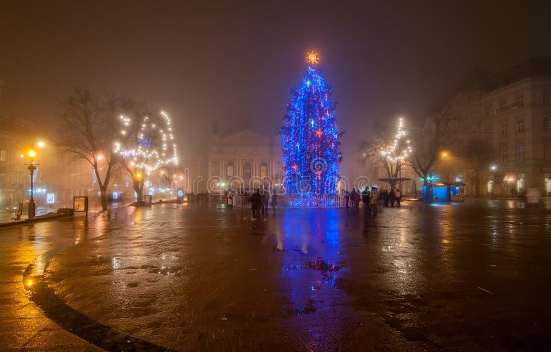Albero di Natale illuminato sulla piazza sulla sera nebbiosa fotografia stock