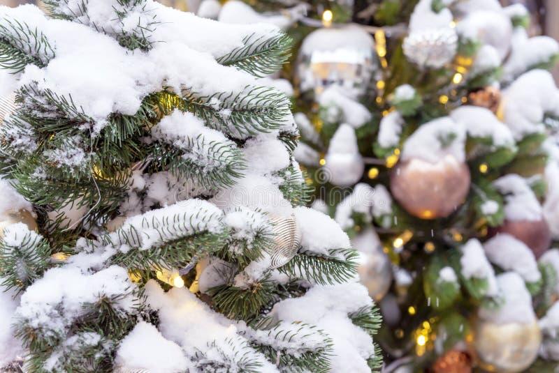 Albero di Natale innevato con i giocattoli e una ghirlanda fotografia stock libera da diritti