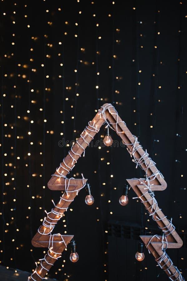 Albero di Natale di legno alternativo Un albero fatto a mano del nuovo anno con la lampadina sul fondo nero delle luci della ghir fotografia stock
