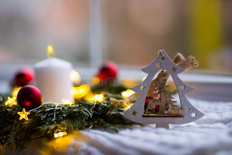 Albero di Natale di legno decorativo con i cervi, la candela bianca bruciante e la corona dell'abete con le palle rosse e le luci fotografia stock