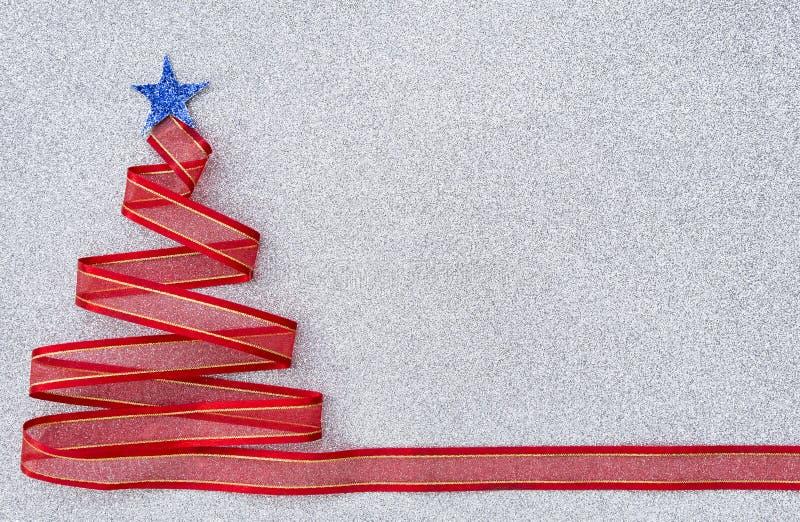 Albero di Natale rosso del nastro con la stella blu sul backbround d'argento di struttura di scintillio fotografia stock libera da diritti