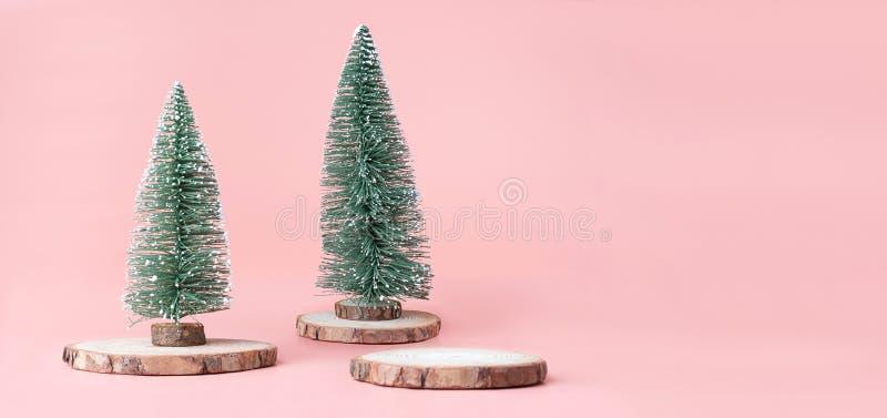 Albero di Natale sulla fetta di legno del ceppo con la scatola attuale sul rosa pastello fotografia stock libera da diritti