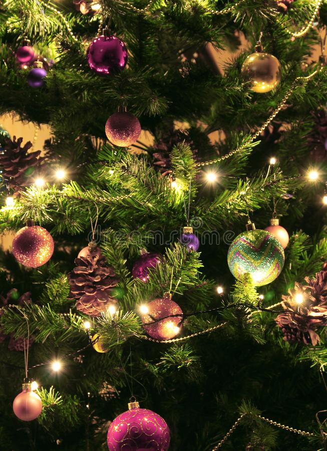Albero di Natale verde con le grandi pigne per fondo orizzontale Decorato con le palle rotonde, le ghirlande e la luce intensa lu immagini stock libere da diritti