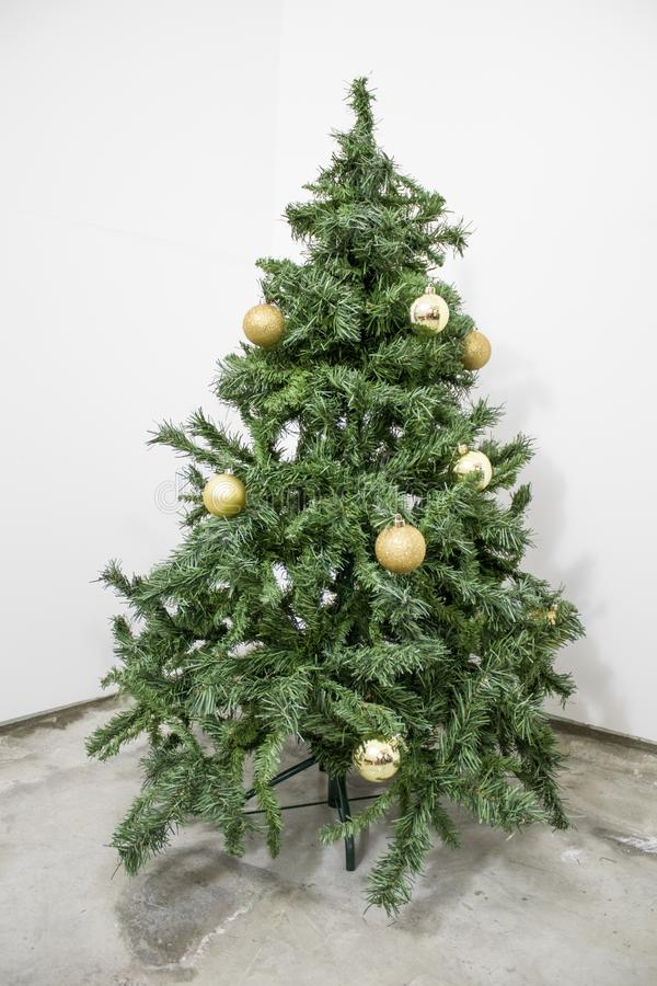 Albero di Natale verde dettagliato con le decorazioni dell'oro in una b bianca fotografie stock
