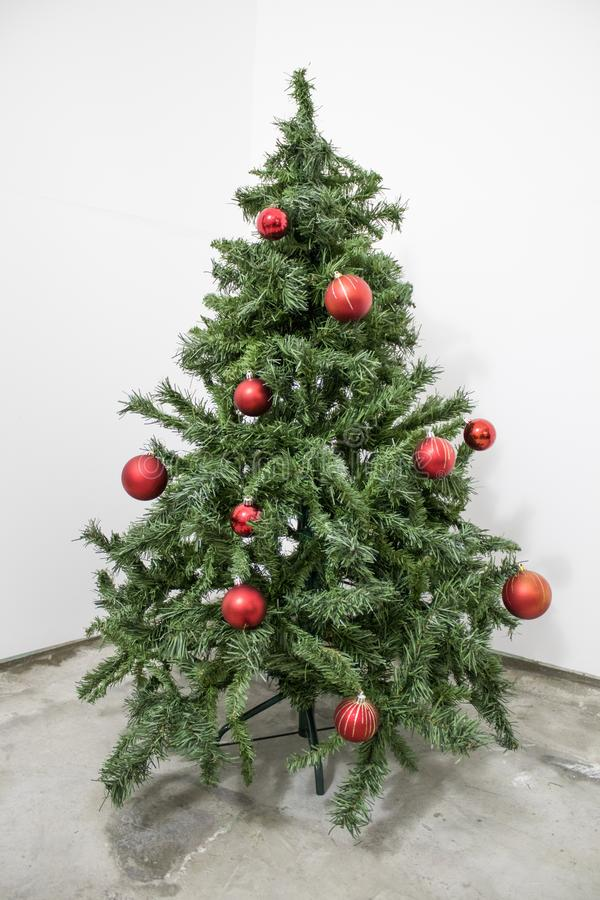 Albero di Natale verde dettagliato con le decorazioni rosse in sedere bianche immagini stock libere da diritti