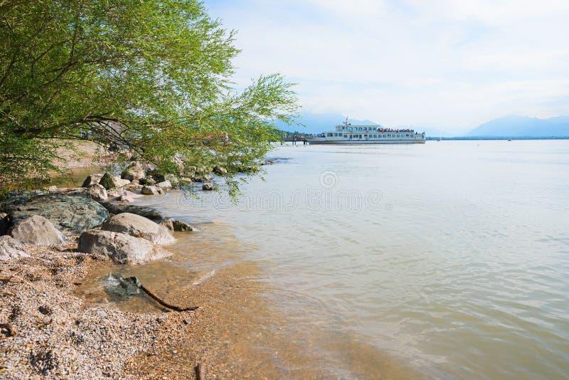 Albero e pietre di salice idilliaco del chiemseewith della riva del lago Vista a immagini stock