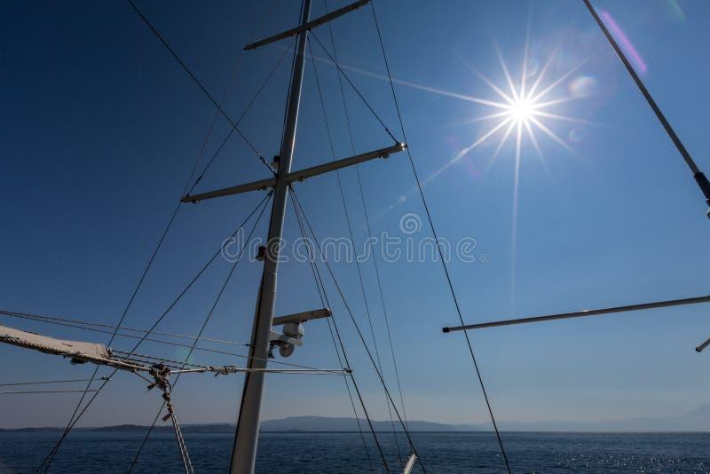 Albero e sartiami sopra cielo blu con il Sun fotografia stock libera da diritti
