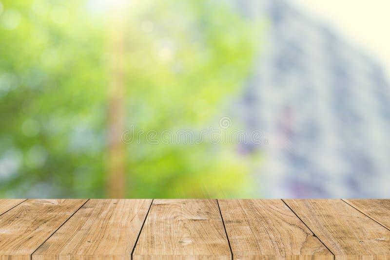 Albero verde della sfuocatura in città con spazio di legno fotografia stock
