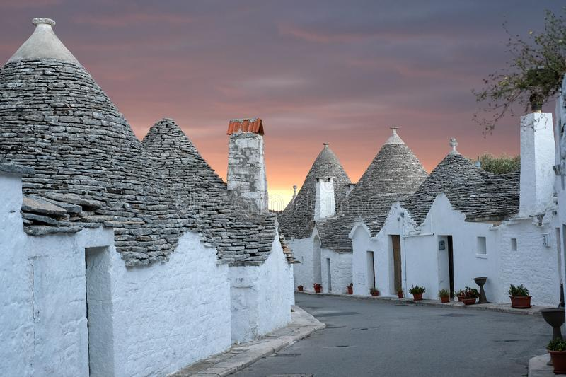 Traditional trulli houses on street in the Aia Piccola area of Alberobello. Photographed early morning with red sky. Alberobello, Puglia, Italy. Traditional dry royalty free stock photos