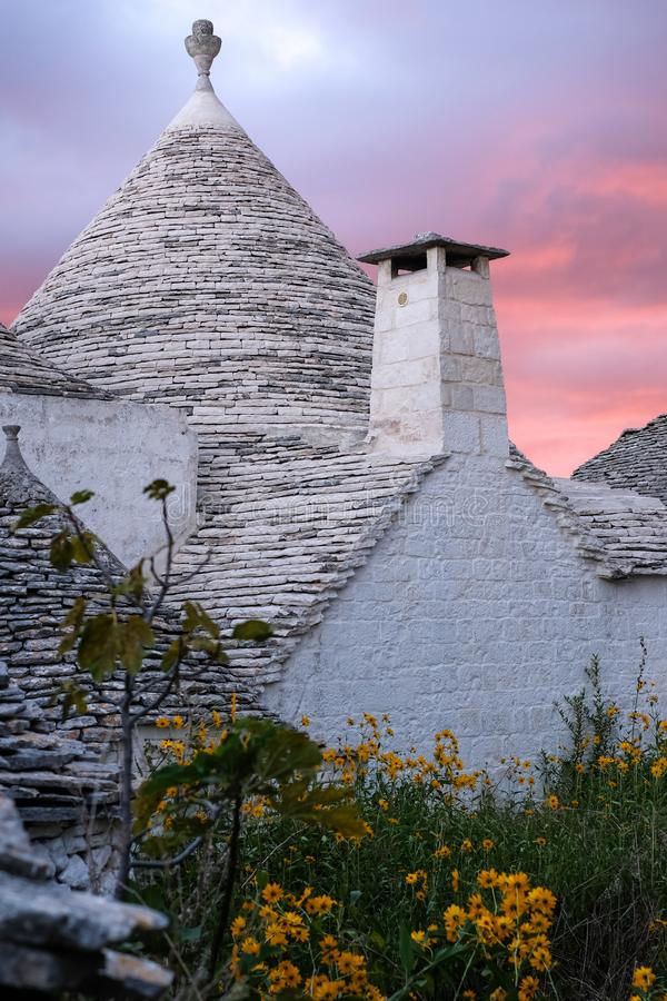 Traditional trulli houses on street in the Aia Piccola area of Alberobello. Photographed early morning with red sky. Alberobello, Puglia, Italy. Traditional dry stock photos