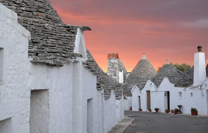 Traditional trulli houses on street in the Aia Piccola area of Alberobello. Photographed early morning with red sky. Alberobello, Puglia, Italy. Traditional dry stock photo