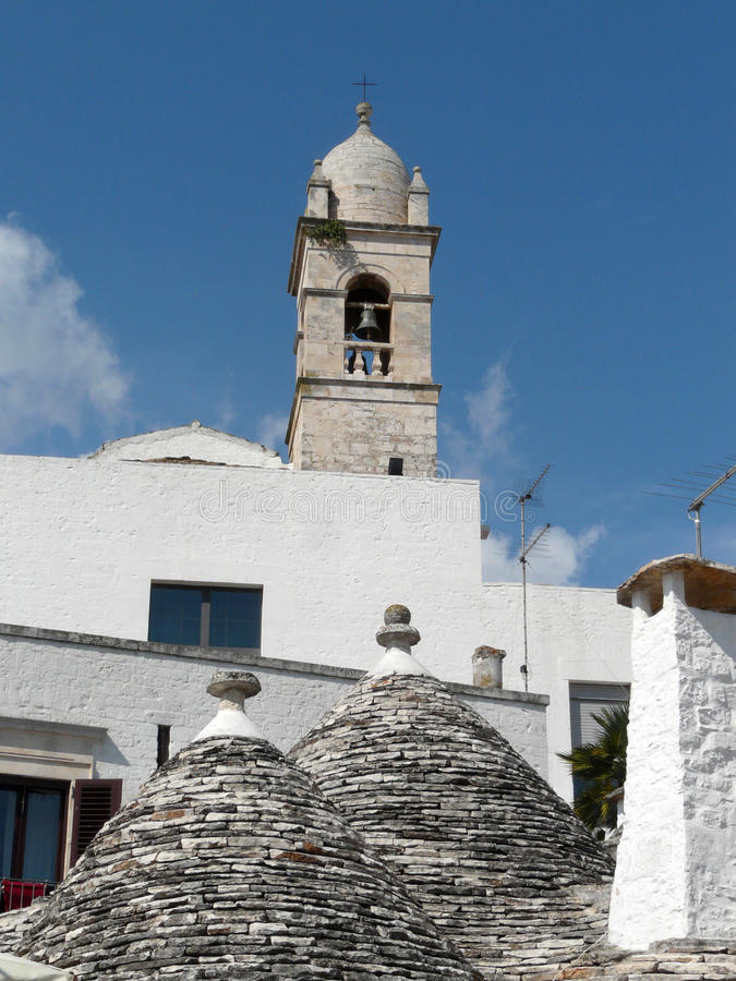 Alberobello's trulli and belltower. Trulli, the traditional houses of the farmers of Alberobello, southern Italy royalty free stock photography