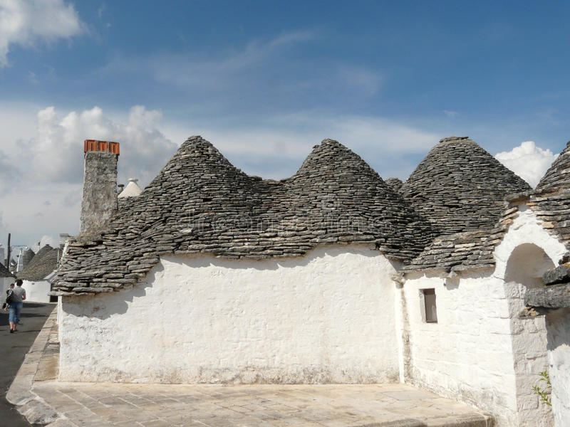 Alberobello's trulli and blue sky. A road of Trulli, the traditional house of the farmers of Alberobello, southern Italy royalty free stock images