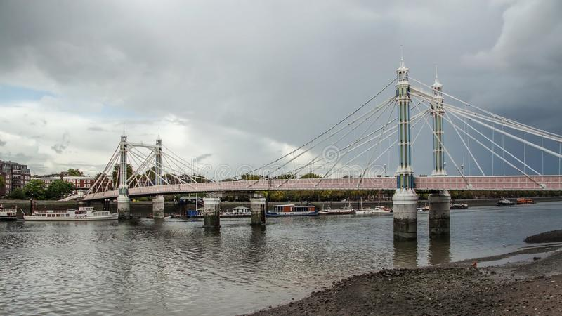 Albert Bridge over river Thames in London on gray overcast day. It connects Chelsea to Battersea and was opened in 1873 royalty free stock photography
