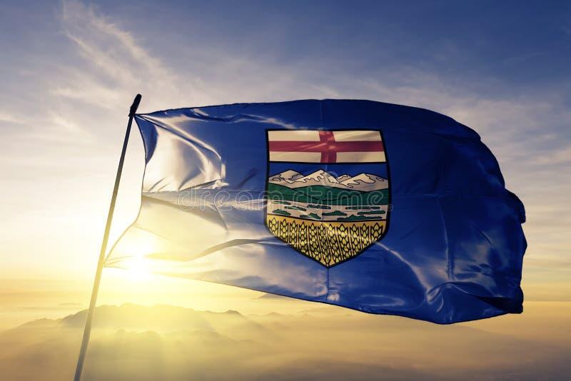 Alberta landskap av tyg för torkduk för Kanada flaggatextil som vinkar på den bästa soluppgångmistdimman stock illustrationer