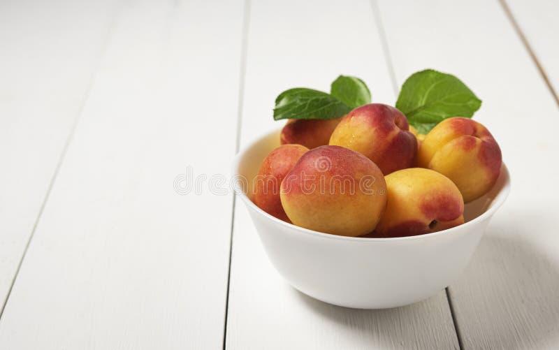 Albicocca deliziosa dolce sulla frutta fresca della ciotola di estate di legno bianca scura della tavola fotografia stock libera da diritti