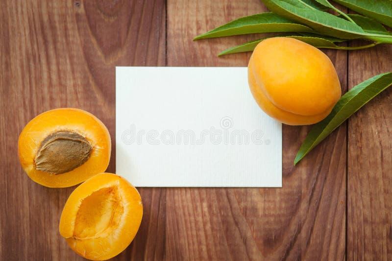 Albicocche mature e carta in bianco per l'iscrizione su una tavola di legno immagine stock libera da diritti