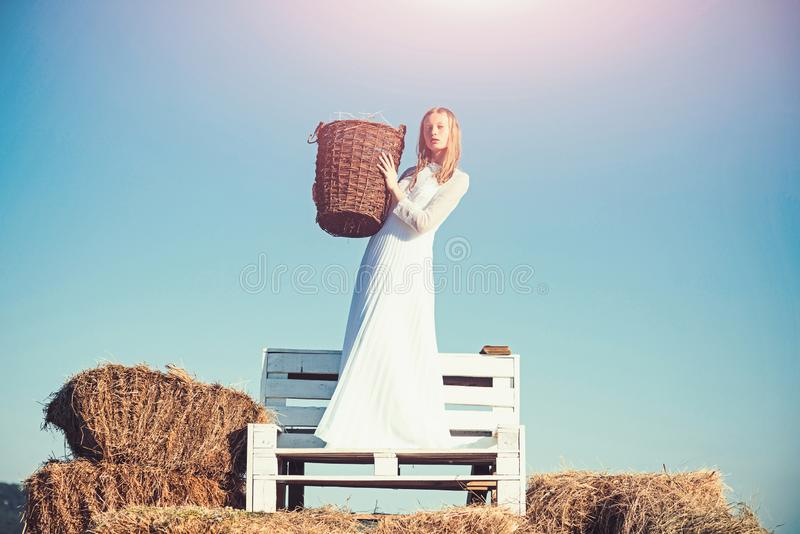 Albino ψάθινο καλάθι λαβής κοριτσιών με το σανό ηλιόλουστο σε υπαίθριο Νύφη γυναικών στο γαμήλιο φόρεμα στον ξύλινο πάγκο Προκλητ στοκ εικόνες με δικαίωμα ελεύθερης χρήσης