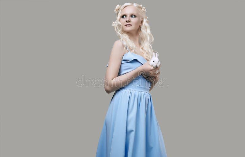 Albino blond girl in elegant dress posing with cute little rabbit royalty free stock photo