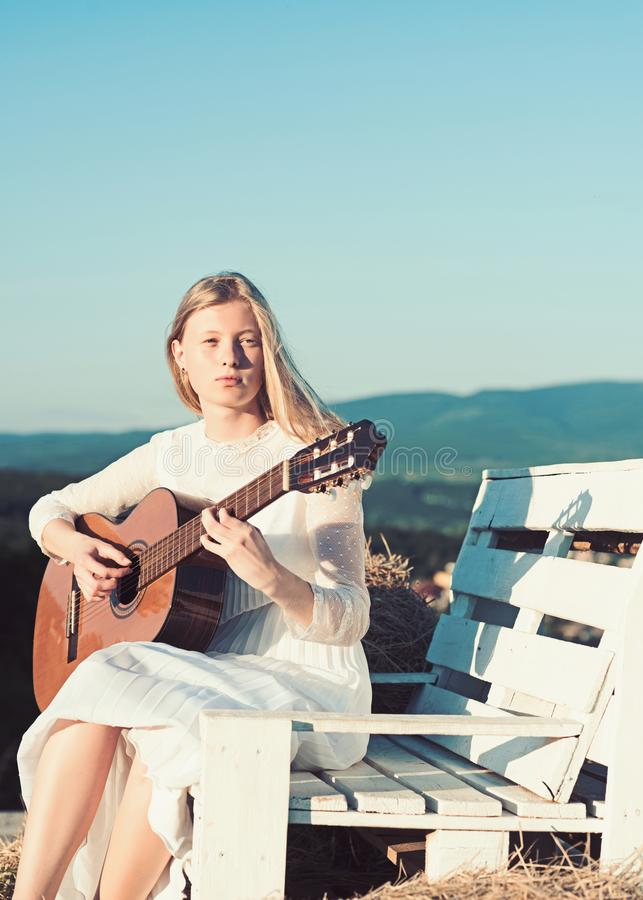 Albino girl hold acoustic guitar, string instrument. Fashion musician in white dress on sunny nature. Sensual woman play stock photos