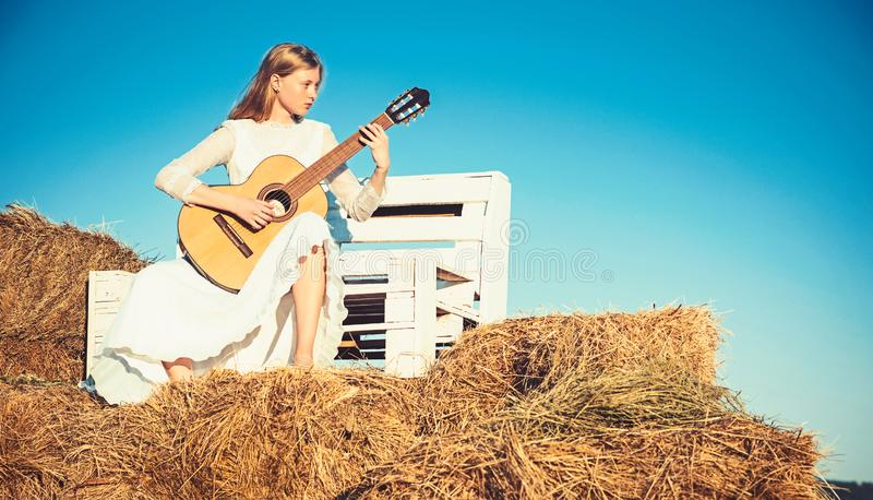 Albino girl hold acoustic guitar, string instrument. Sensual woman play guitar on wooden bench. Woman guitarist perform royalty free stock photos