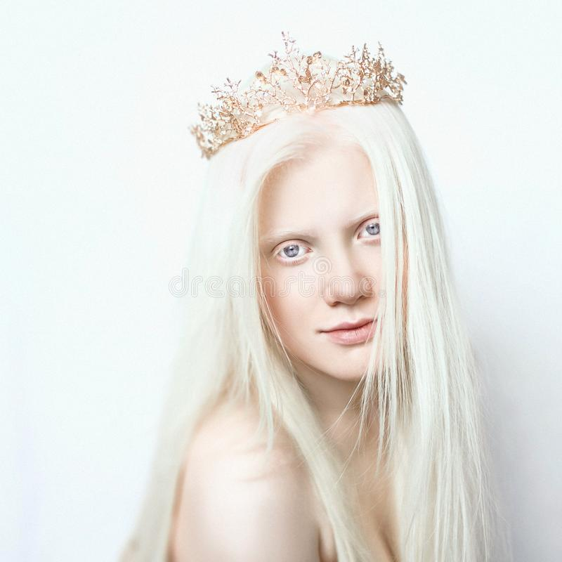 Albino girl with white skin, natural lips and white hair. Photo face on a light background. Portrait of the head. Blonde girl stock photography