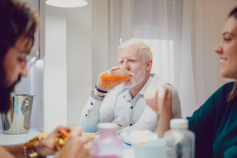 Albinoman som dricker fruktsaft på matställen med vänner royaltyfri bild