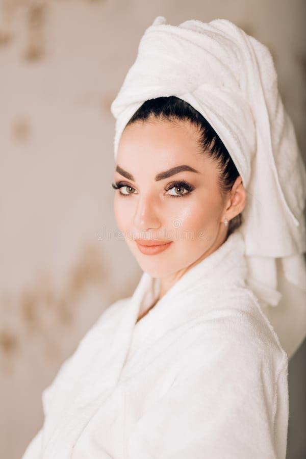 Albornoz blanca que lleva y toalla de la muchacha atractiva en la cabeza en cuarto de baño foto de archivo