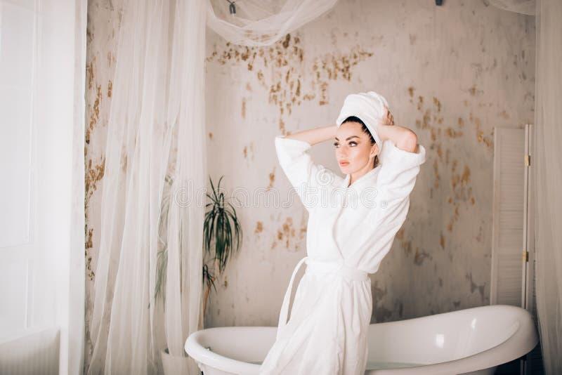 Albornoz blanca que lleva y toalla de la muchacha atractiva en la cabeza en cuarto de baño imagen de archivo