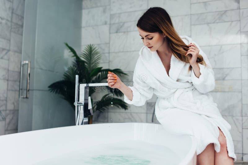 Albornoz que lleva de la mujer bastante delgada que se sienta en el borde de la bañera que se llena de agua imágenes de archivo libres de regalías