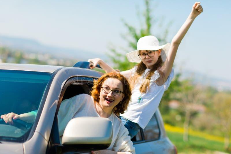 Alborotadores detr?s de la rueda - gamberros femeninos en el coche imagen de archivo libre de regalías